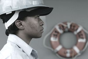 Female boatswain's mate standing at attention on board a ship.