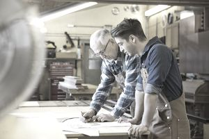 Senior carpenter working with apprentice in workshop