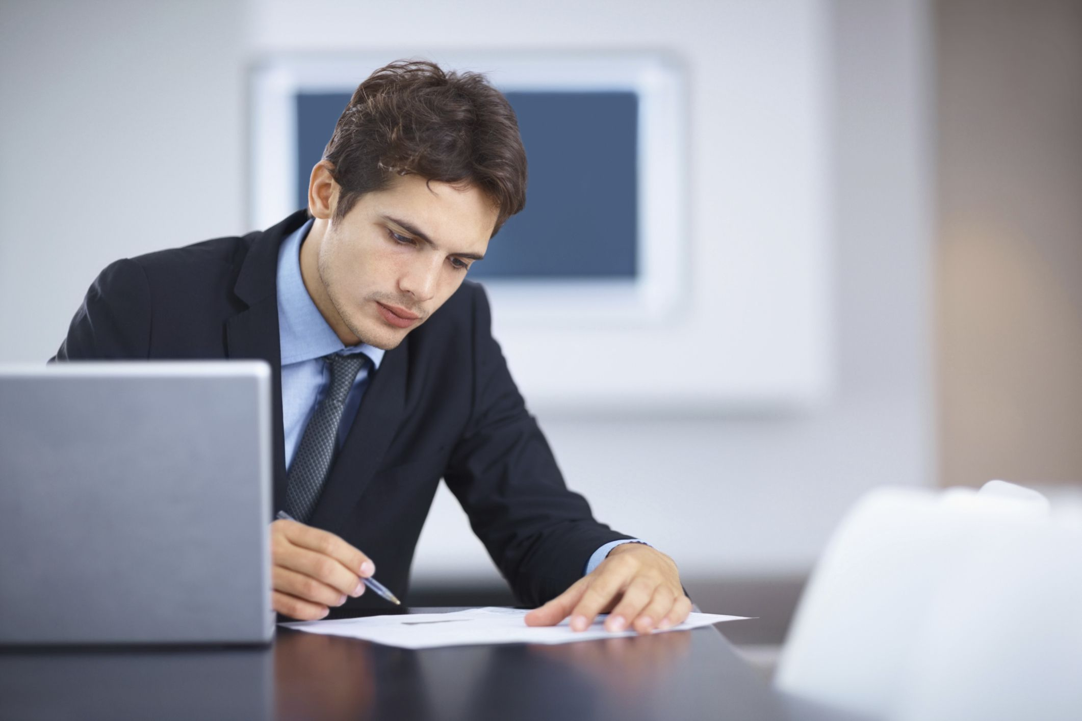 Business man filling out paper on desk in an office