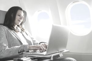 Businesswoman using laptop in business class airplane cabin