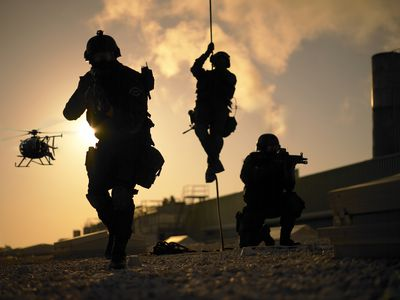 SWAT police unit dropping from a helicopter in the sunset