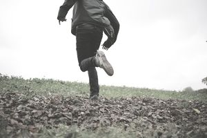 Young man running through field