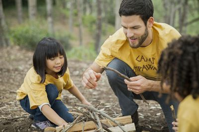 Man in Camp Chipawa t-shirt helping two children build a fire as a camp counselor