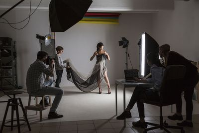 Photography team and model in low key photography studio shoot