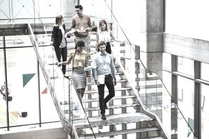 A group of businesspeople walking down the stairs in the modern building, talking.