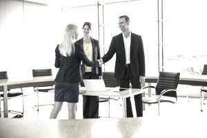 Salesperson shaking hands with contacts from her book of business