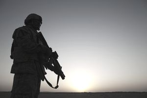 Silhouette of a US soldier at sunrise holding a Metal Storm firearm.