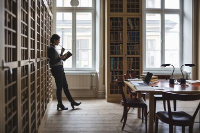 Thoughtful lawyer holding book while leaning on shelf in library