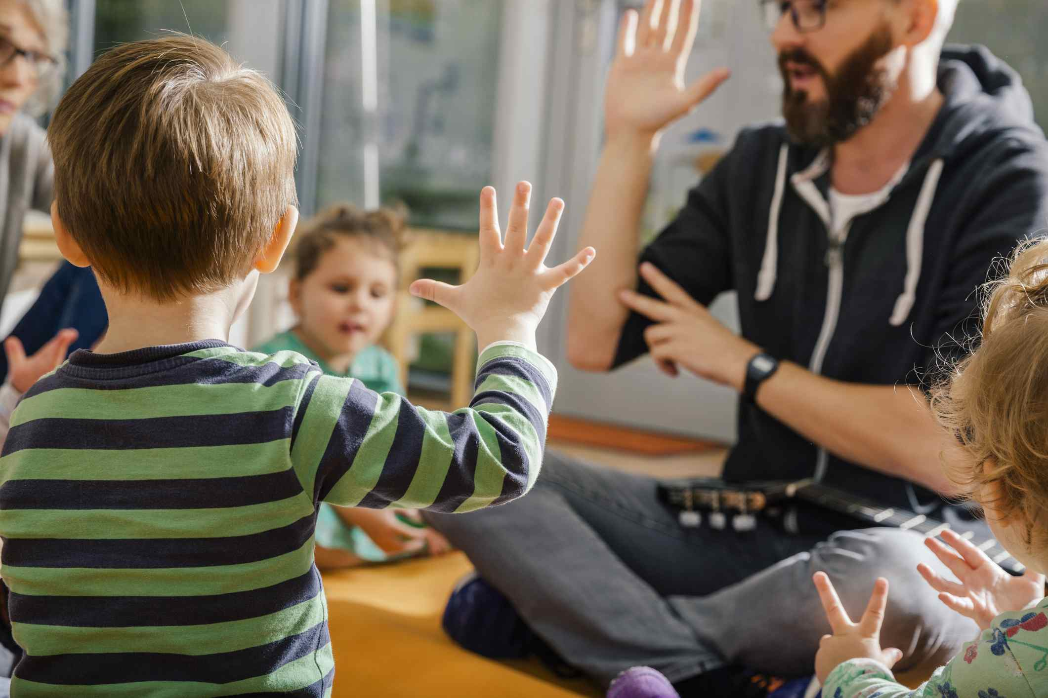 Child raising hand singing with others and teacher in kindergarten