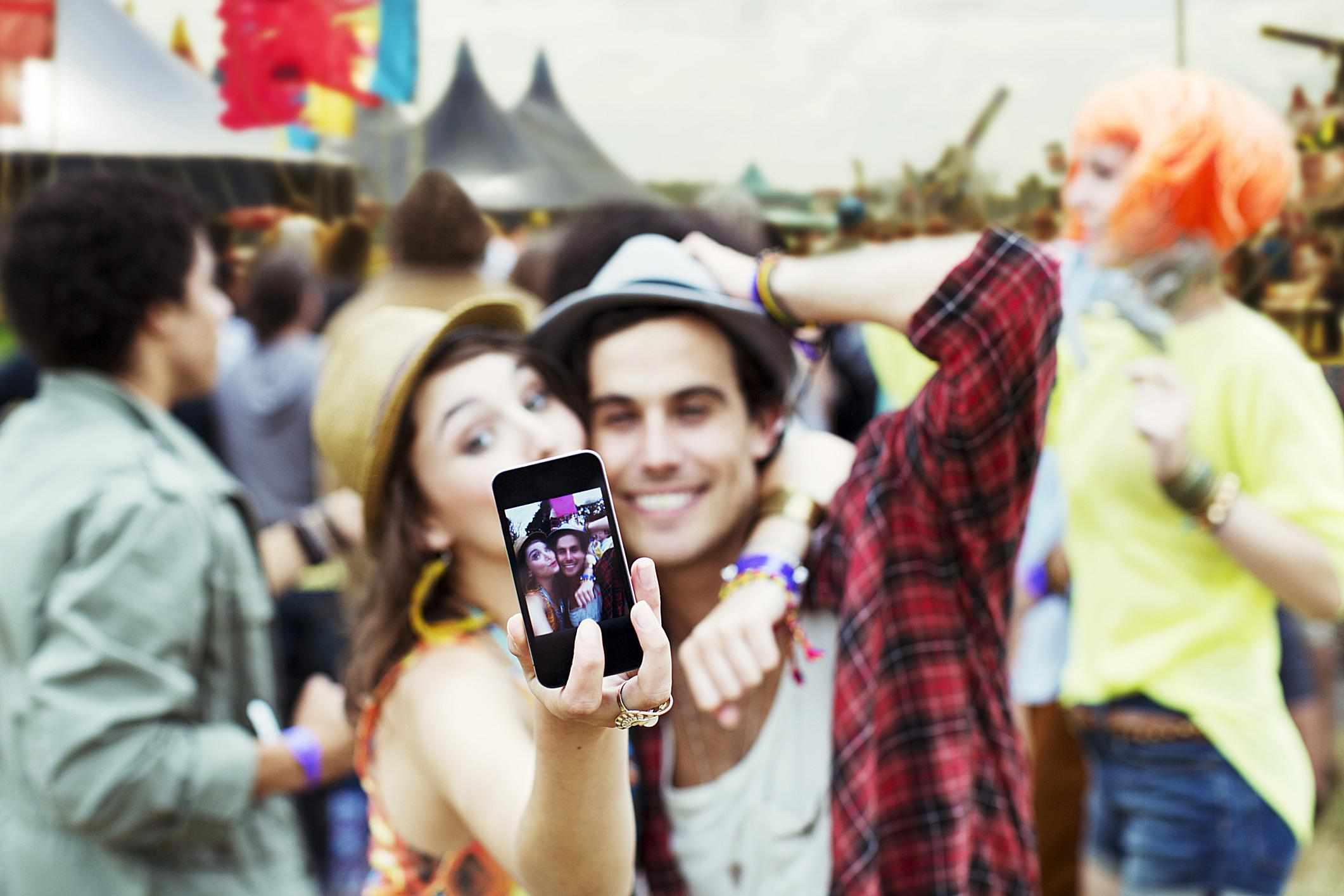 People taking a selfie at a music festival