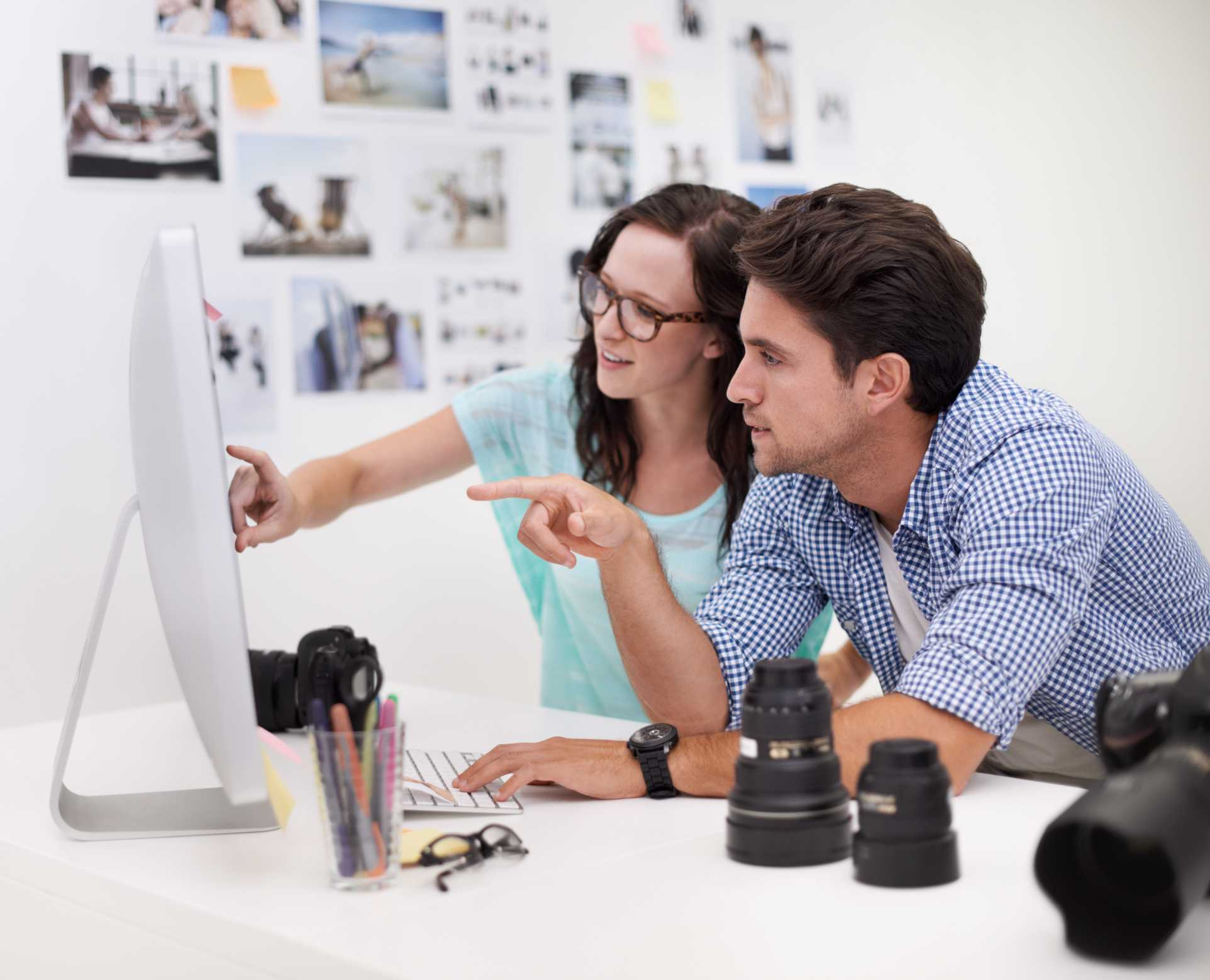 Two model bookers pointing at photos on a computer monitor.