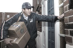 U.S. Postal Service carrier ringing doorbell and carrying boxes
