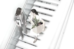 Businesswoman Carrying Cardboard Box on Staircase With Colleague