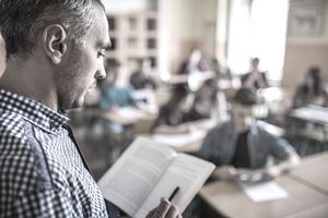 Profile view of a professor using a book on a lesson in the classroom.
