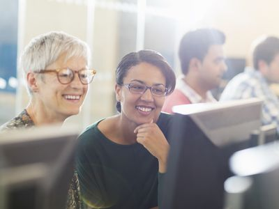 Smiling women at computer in adult education classroom