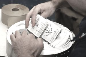AT SEA - DECEMBER 30: Cryptologic Technician 1st Class, Steve Reed, prepares leaflets for distribution to Iraqi military personnel in Iraq December 30, 2002 while onboard the USS Constellation. Coalition aircraft are dropping leaflets like these primarily over southern Iraq. According to the U.S. Navy, this is the first time leaflets of this type have been printed and prepared aboard a U.S. Navy ship. Messages on the leaflets provide the Iraqi military personnel with radio frequencies to listen to for Coalition information. Other leaflets warn Iraqi antiaircraft batteries not to fire on Coalition aircraft.
