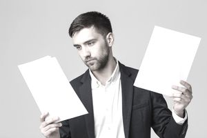 Handsome Businessman Examining Paperwork While Standing Against Gray Background
