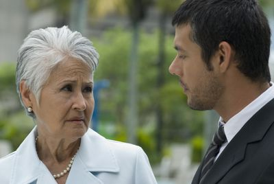 An older employee complains to a younger manager who looks disinterested in what they have to say.