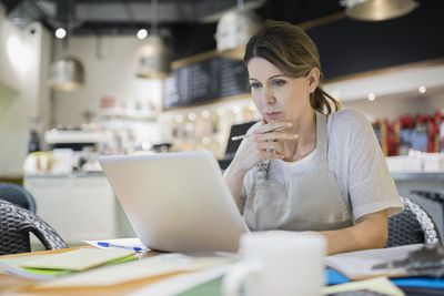 Serious business owner working at laptop in cafe