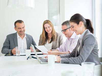 Employees with varying degrees of seniority sitting at a conference table in an office.