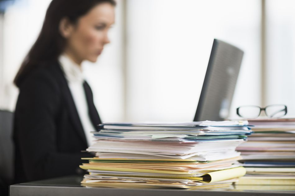 An office worker with a pile of folders with paperwork on her desk.