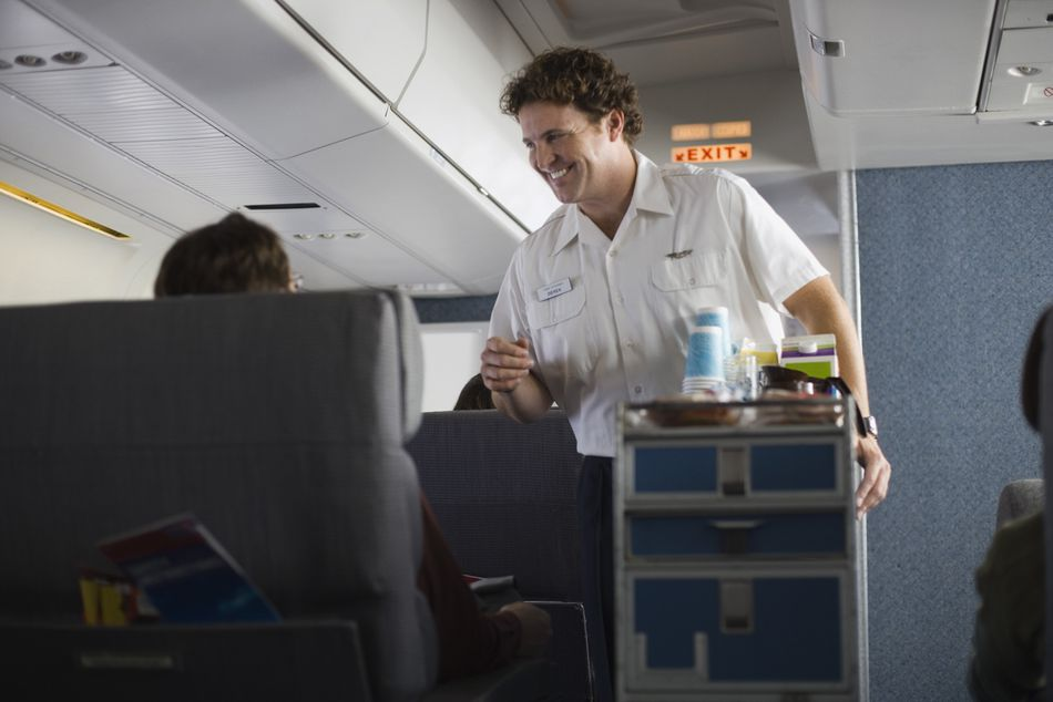 Flight attendant serving passengers on airplane
