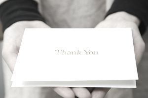 A woman holding a thank you card