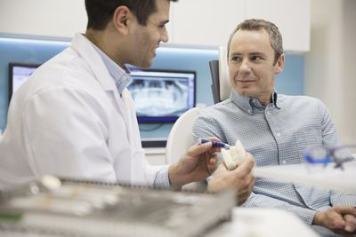 Dentist showing patient tooth model in office