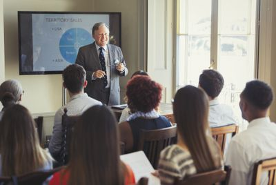 Businessman leading sales training at television screen