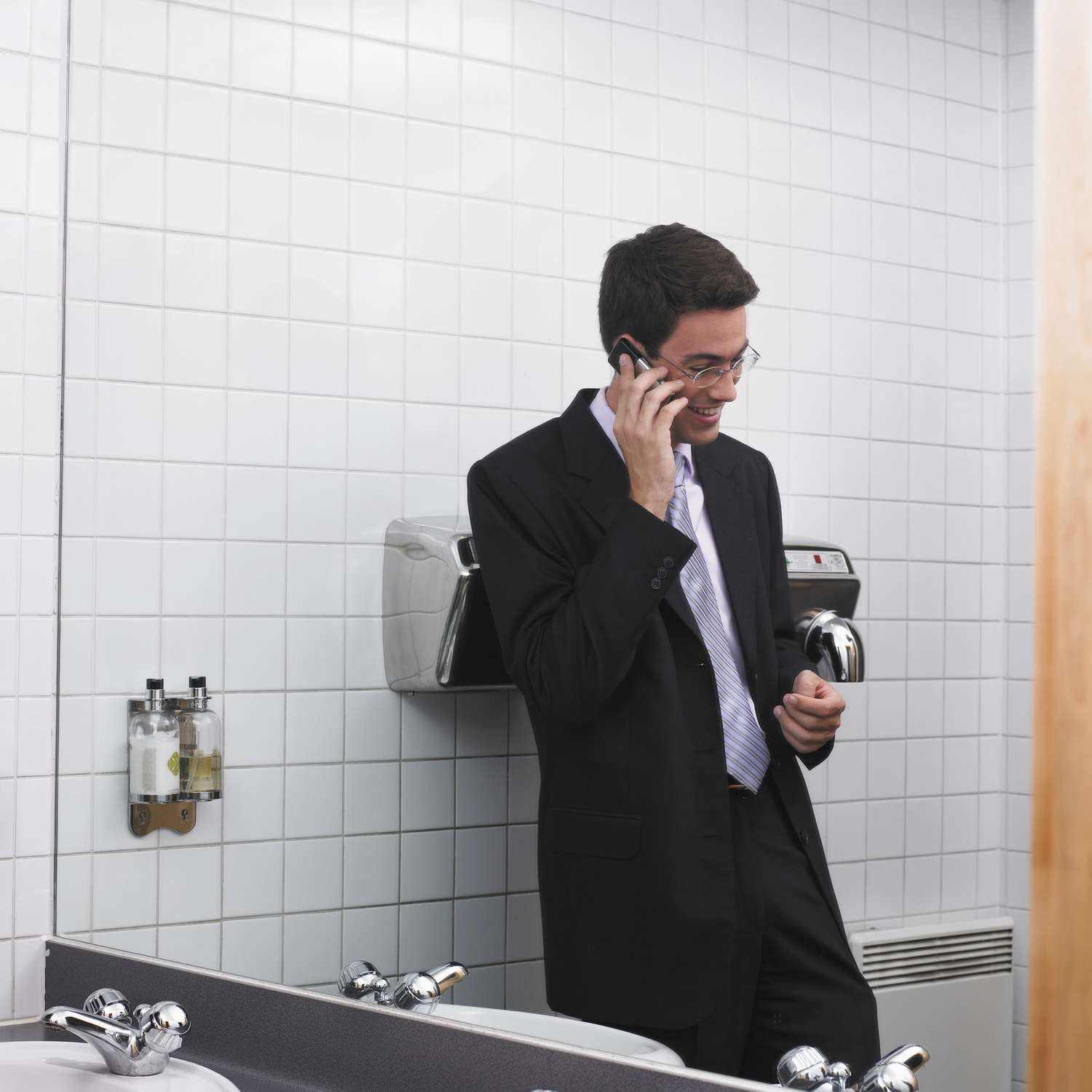 Man talking on his cell phone in the workplace bathroom.