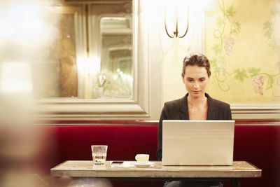 Young businesswoman working on laptop in cafe