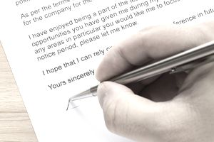 A hand signing a resignation letter