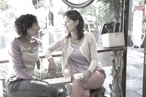 Two women talking together in a cafe