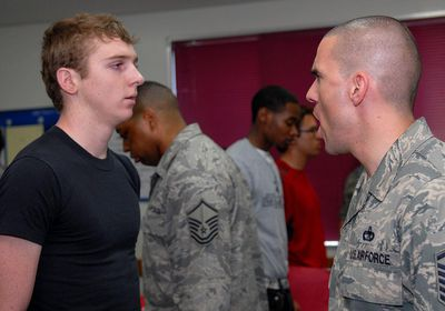 A U.S. Air Force Military Training Instructor yelling at a trainee. The orientation is intended to mentally prepare the young men and women for what they can expect upon arrival at Lackland Air Force Base for USAF Basic Military Training.