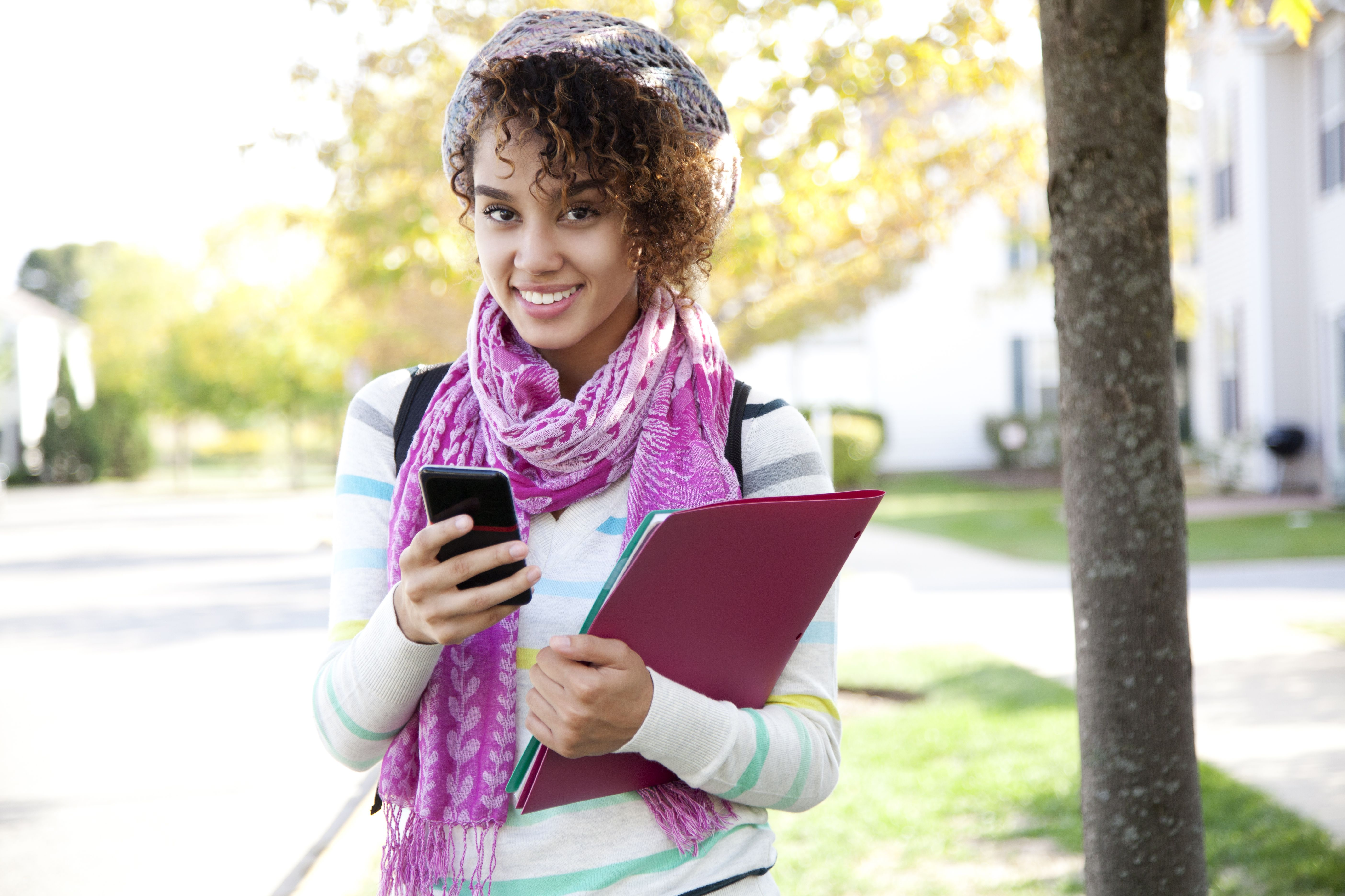 Student with folder and phone