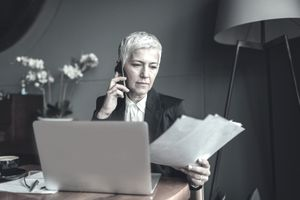 Mature Businesswoman Talking On The Phone And Examining Documents.