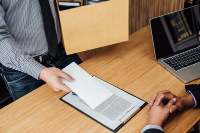 Midsection Of Employee Giving Resignation Letter To Manager Sitting On Desk