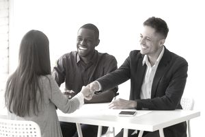 Smiling hr handshaking female applicant at job interview, hiring concept