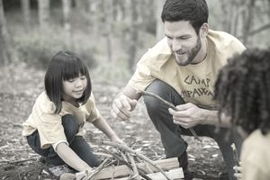 Camp counsellor and students preparing campfire together in forest