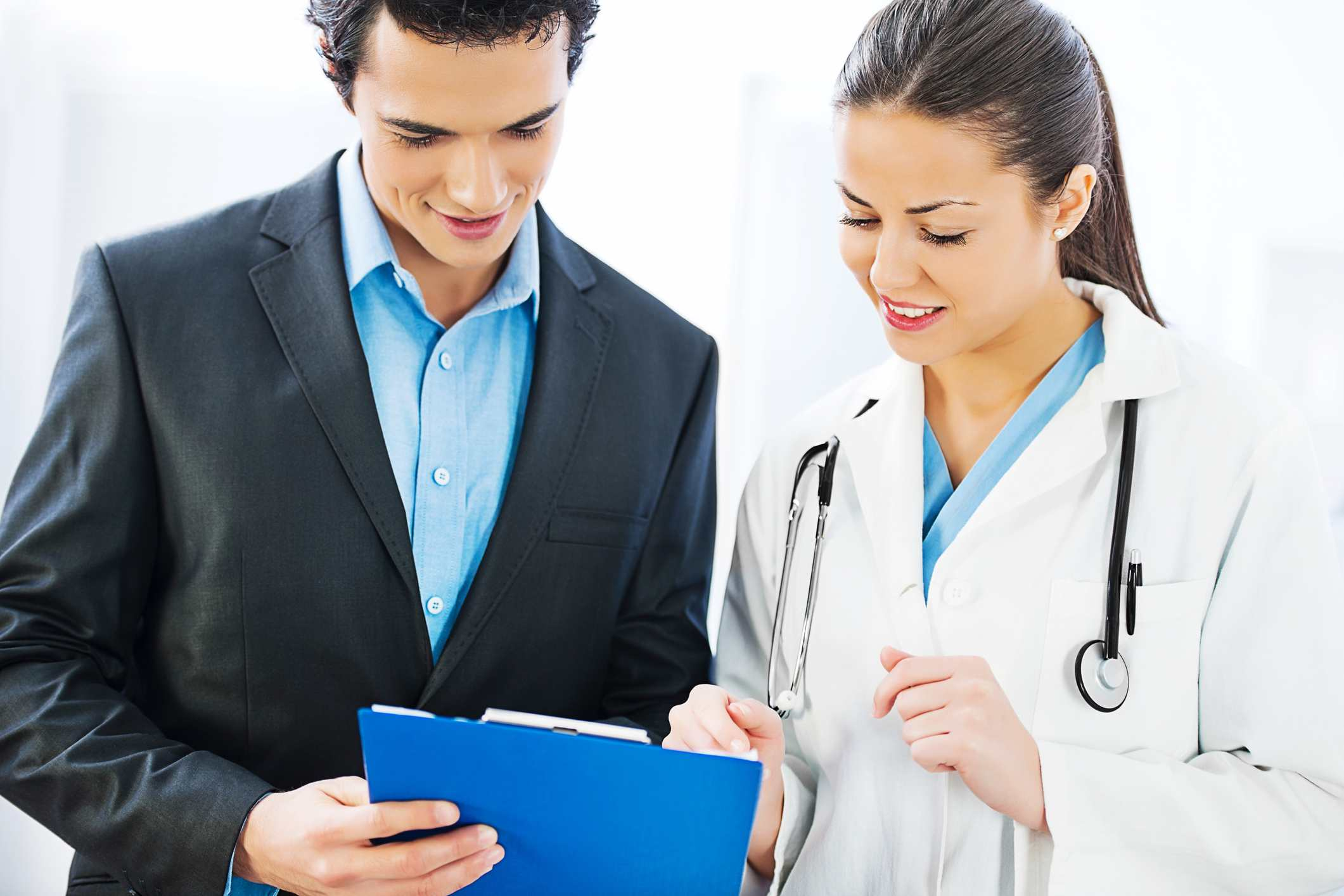 doctor explaining medical treatments and insurance form to patient