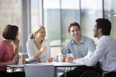 Four work colleagues chatting over lunch or break in the office canteen