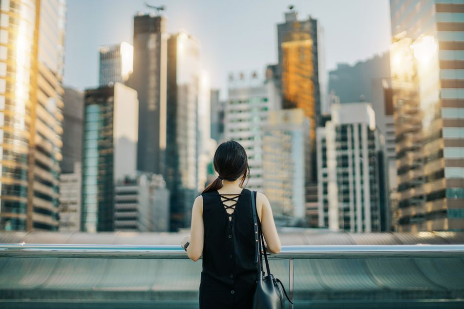 Rear view of woman looking out over urban cityscape against sky