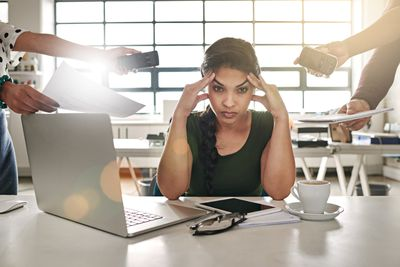 Manager at desk looking stressed as several employees ask for help