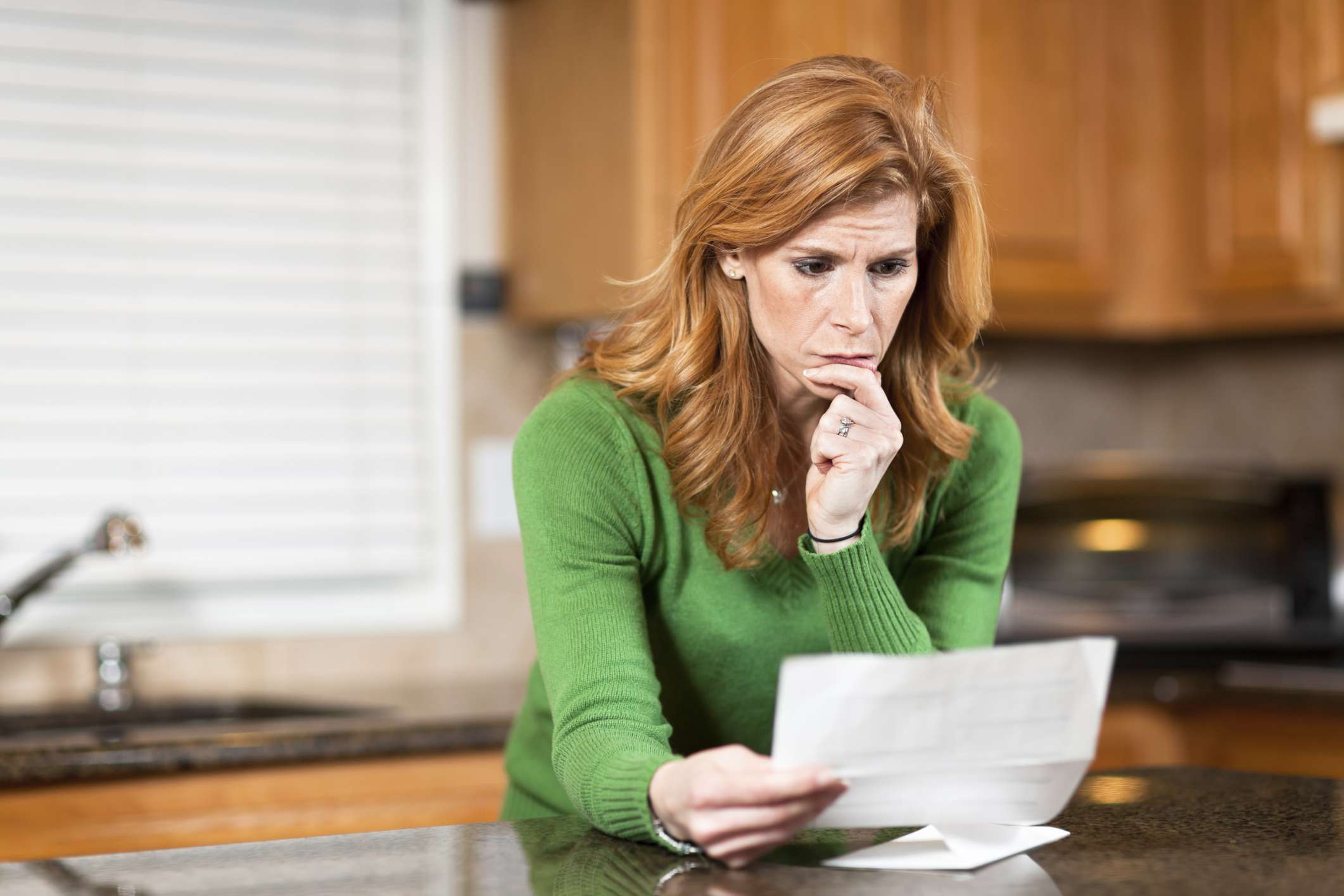 Tthoughtful woman reading paper