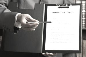 lawyer handing over pen to sign divorce agreement