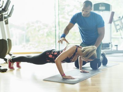 male personal trainer training a woman doing plank exercise
