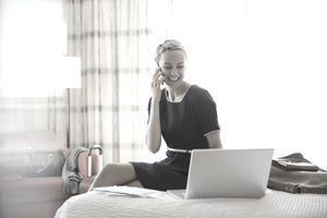 Businesswoman using wireless devices in hotel room