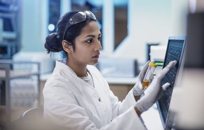 Female scientist working in a lab, using a computer screen.