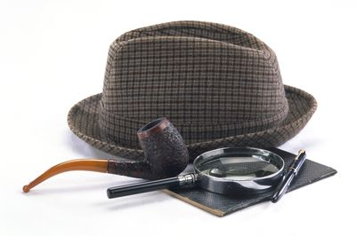 Sherlock Holmes style detective's hat, pipe, magnifying glass and pen