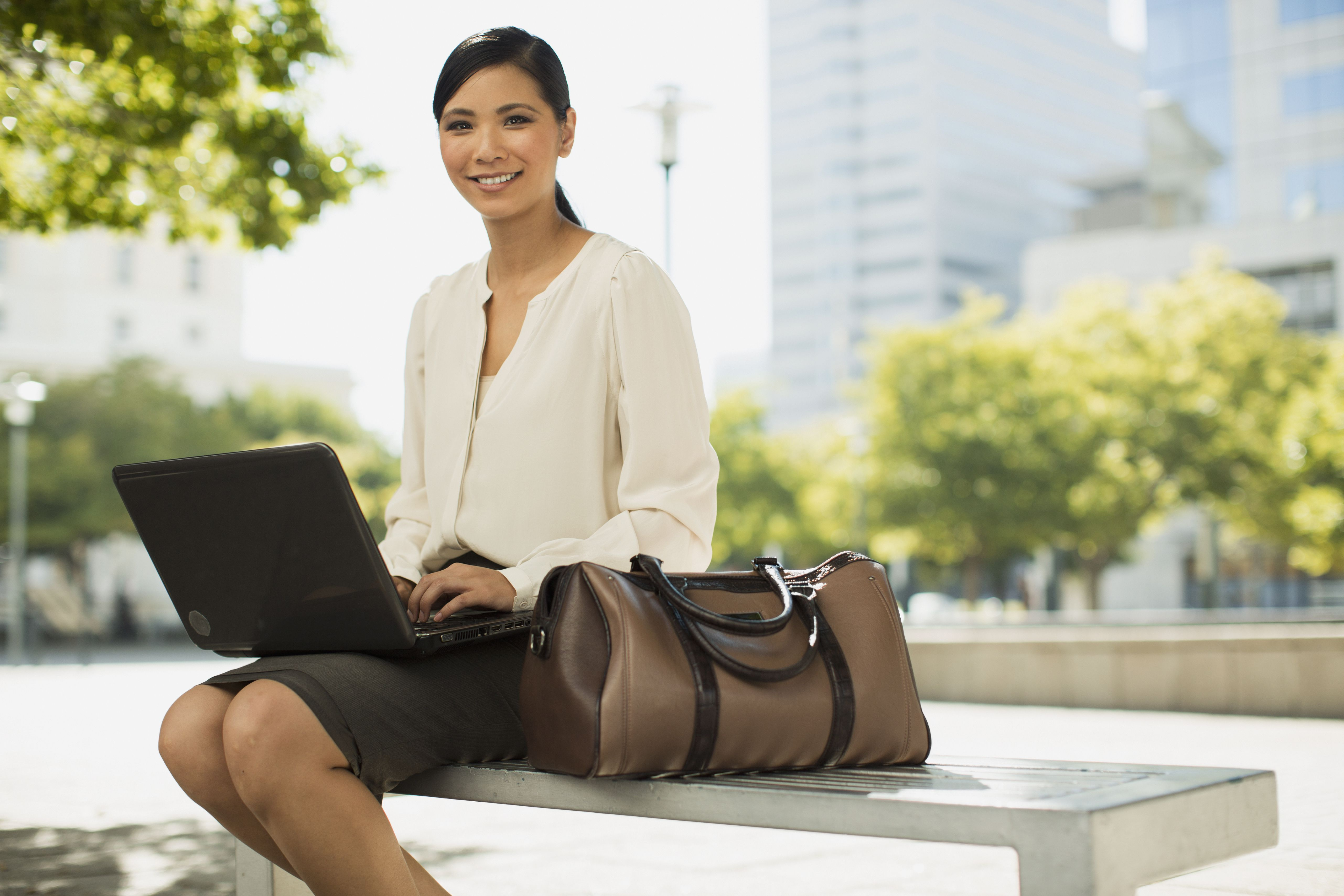 Smiling businesswoman using laptop in park wearing formal business attire.